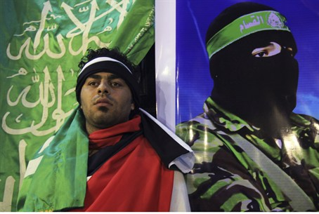 man poses next to poster of Hamas terrorist