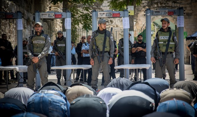 Muslim worshipers bow to soldiers while praying near Temple Mount