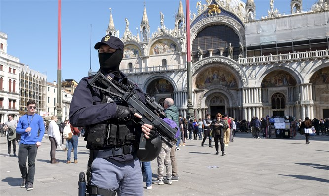 Italian masked police officer patrols in St. Mark's square in the Venice lagoon