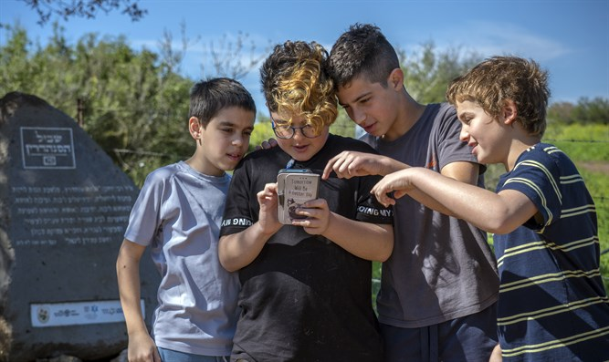Students examine the Sanhedrin Trail web application next to one of its smart stones.