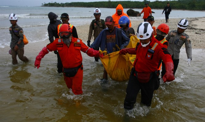 Rescue workers carry a body bag containing the remains of a victim of tsunami