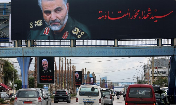 Vehicles pass picture of late Iranian Major-General Qassem Soleiman